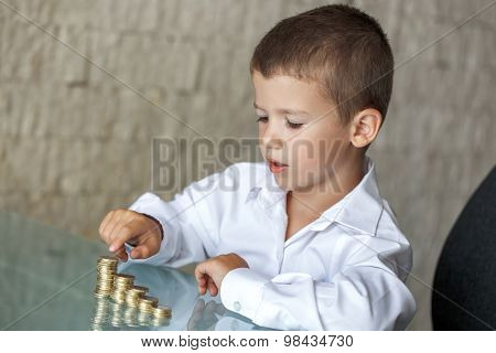 Little Boy Counting Coins On Glass Desk