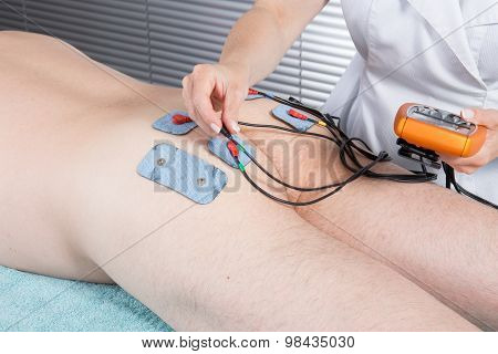 High Angle View Of Therapist Placing Electrodes On Man's Bottom