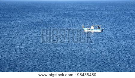 Lonely Fishing Boat On A Calm Blue Sea
