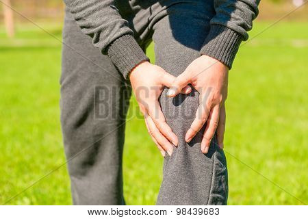 Male Hands Clasped Sore Knee Outdoors
