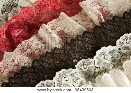 Closeup of white red and ivory vintage lace fabrics