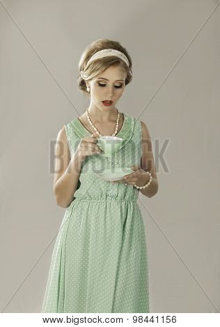 Retro fifties blonde woman drinking tea