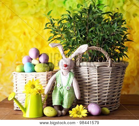 Easter bunny with painted Easter eggs with flowers on wooden table on yellow  background