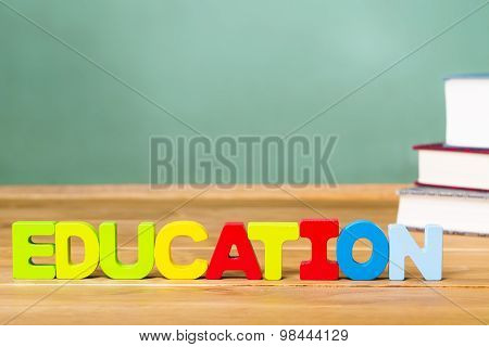 Education Theme With Textbooks And Green Chalkboard