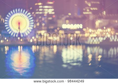 Blurred Bokeh Harbor Lights Background At Night With Ferris Wheel