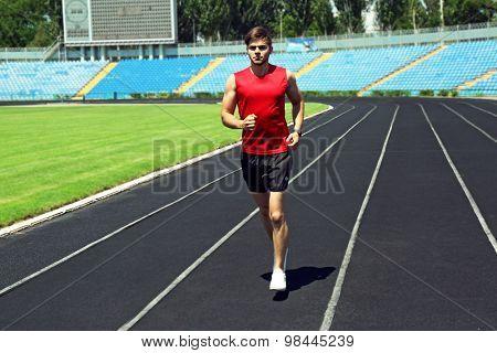 Young man jogging on stadium