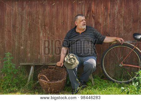 senior farmer sitting on a bench at summer day