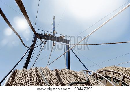 Close Up View Of Network Fishing Ropes Of Boat Stranded Under Summer Blue Sky In Sea Industry