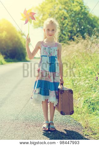 Little Girl With Pinwheel And Suitcase On Rural Road.