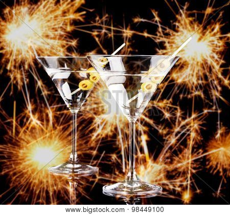 Cocktails in martini glasses on bright sparklers background