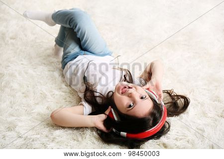 Beautiful little girl listening to music in room