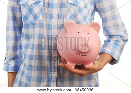 Female hands with pink piggy bank, closeup
