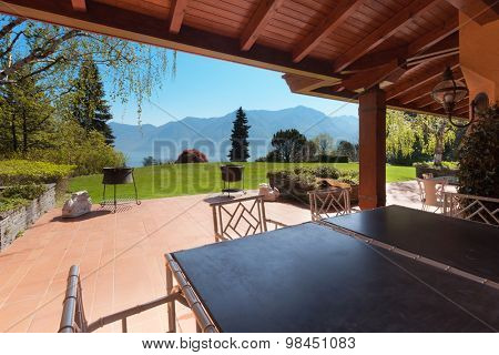 veranda of a villa with garden in a sunny spring day