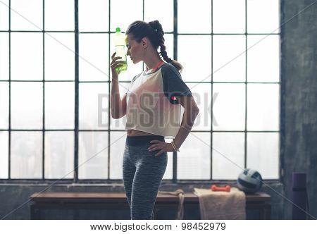 Woman By Window In Loft Gym Holding Water Bottle To Head