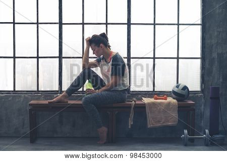 Tired, Fit Woman Resting Head On Hand Sitting In Loft Gym