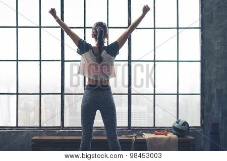 Rear View Of Rejoicing Woman Standing By Window In Loft Gym