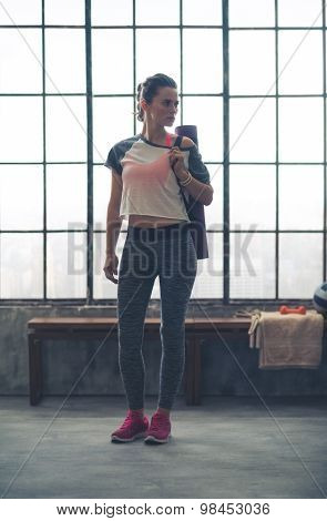 Fit Woman In Workout Gear Standing In Loft Gym Looking Sideways