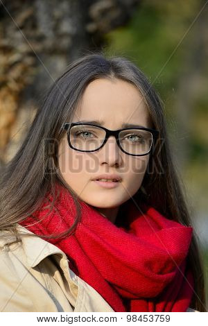 Beautiful young blond woman with glasses and a tense look in her eyes