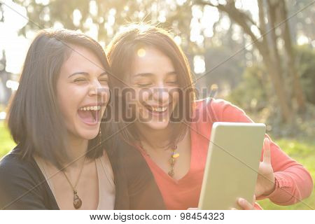 Two beautiful young women laughing and having fun while browsing a tablet