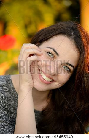Summer portrait of a beautiful freckled young woman smiling with colorful background