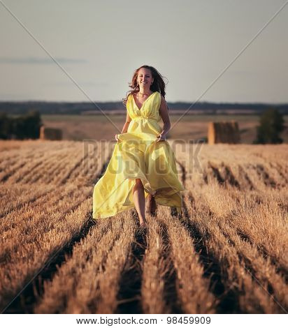 girl in a beautiful dress running at the mown wheat field