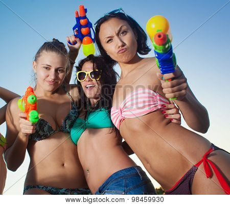 three young girls  playing and posing with water pistols on the beach