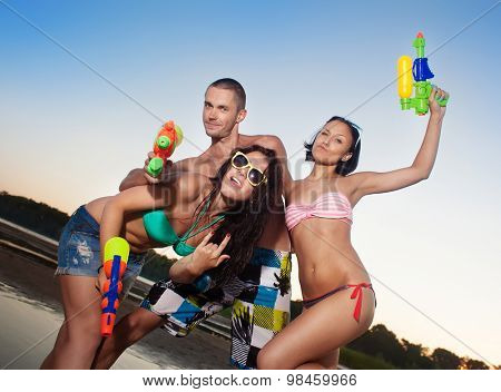 Group of young joyful young people playing with water pistols on the beach