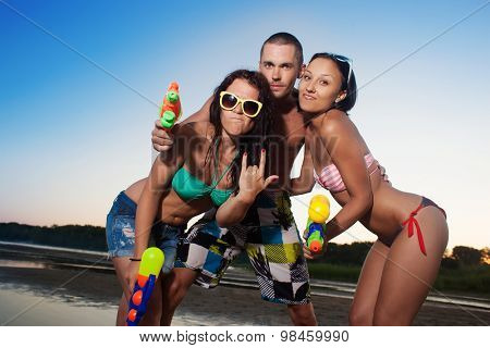 Group of young joyful young people playing and posing with water pistols on the beach