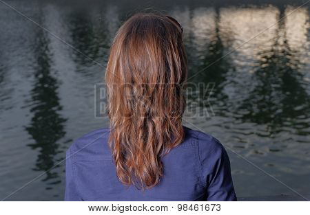 Red haired women rear view. She look at view in city park in calm state of mind.