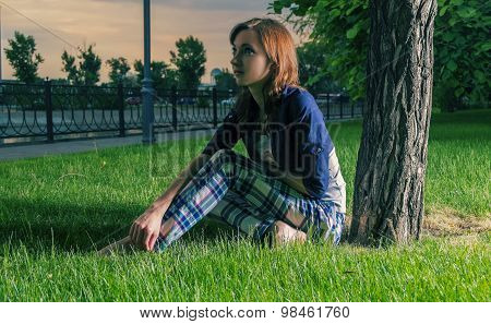 Young boho redhead girl sitting on grass backlit and looking away. Sunset colorful light.