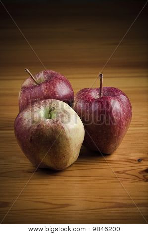 Three apples on wooden table