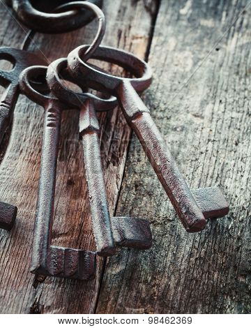 Old Rusty Keys On Wooden Background.