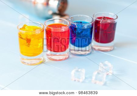 Set of alcoholic cocktails with metal shaker on white bar counter or light background. Selective foc