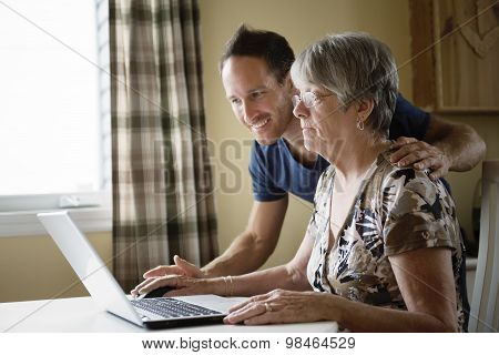 senior woman working on her laptop in her kitchen table