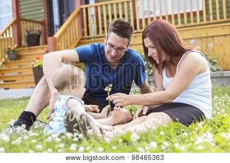 Portrait of couple with their adorable daughter in front of house