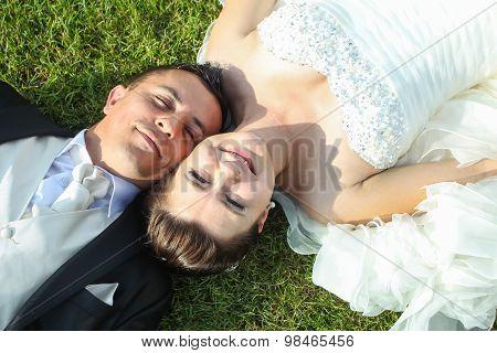 Newlyweds Lying On Grass