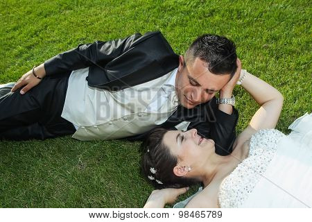 Bride And Groom Resting On Grass