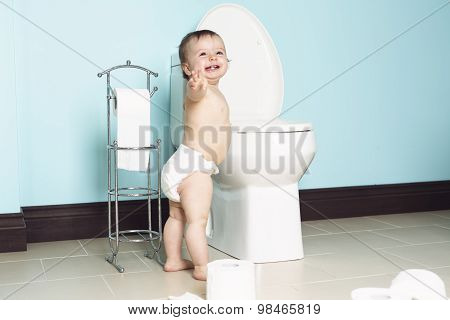 Toddler in bathroom look at the toilet