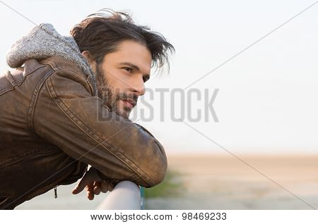 Closeup of thinking man leaning on railing outdoor