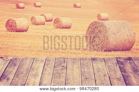 Vintage Toned Hay Bales On A Field With Wooden Boards.
