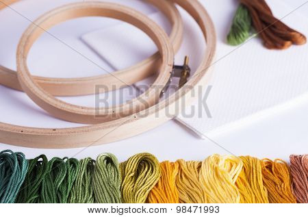 Embroidery Yarns And Hoops On Fabric Background