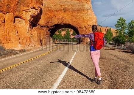Hitch-hiking girl with rucksack near Red canyon