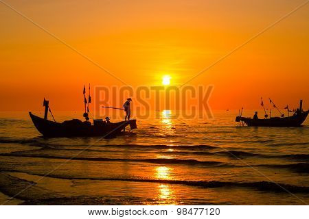 Fishermen on boat in sunrise with big sun