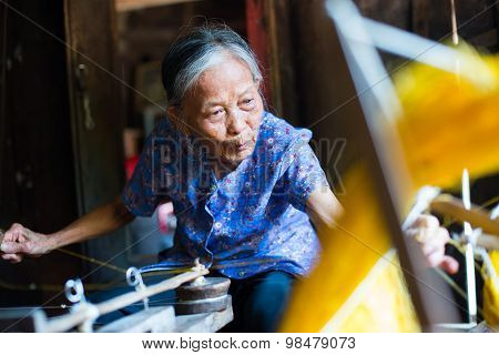 Old woman are weaving silk