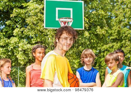 Smiling boy with friends behind during basketball