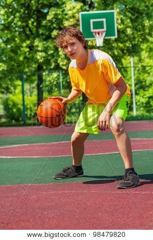 Boy playing with ball alone during basketball game