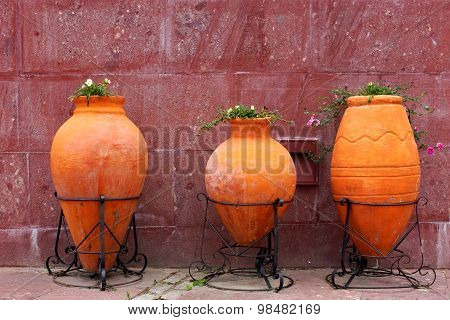 Three Large Clay Jars With Flowers On The City Street