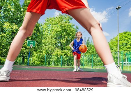 Girl with ball view between two legs of player