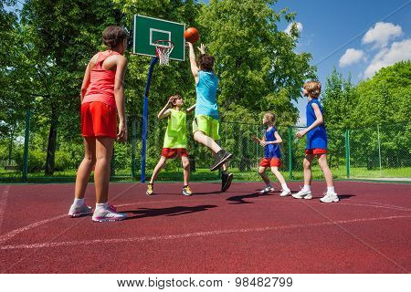Team in colorful uniforms playing basketball game