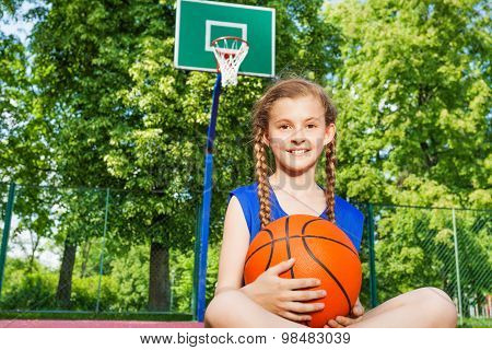 Smiling girl sitting on playground holding ball